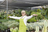 Portrait of a senior woman standing with arms outstretched in garden center — Stock Photo