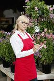Portrait of a senior florist making notes in garden center — Stock Photo