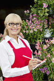 Portrait of a happy senior florist making notes in greenhouse — Stock Photo