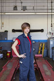Portrait of a young female mechanic standing with hand on hip in car workshop — Stock Photo