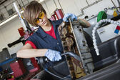 Young female mechanic working with welding torch on vehicle machinery part in auto repair shop — Stock Photo