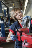 Young female mechanic in protective workwear working on machinery part in automobile repair shop — Stock Photo