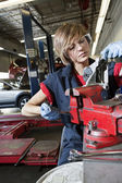 Young mechanic in protective clothing concentrating on repairing machine part in garage — Stock Photo