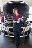 Young female mechanic reading paper with open bonnet of car in garage — Stock Photo