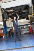 Young female mechanic working while standing under lifted car in workshop — Stock Photo