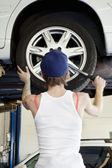Back view of young female mechanic working on lifted car's tire in automobile repair shop — Stock Photo