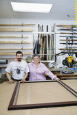 Portrait of happy senior owner with mature employee in frame workshop — Stock Photo