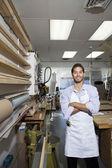 Ritratto di felice operaio esperto in piedi con le braccia incrociate in officina — Foto Stock