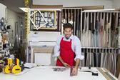 Porträtt av glad yrkesarbetare mäta med mätaren stick i workshop — Stockfoto