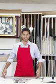 Retrato de feliz joven trabajador calificado permanente con palo medidor en taller — Foto de Stock