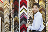 Portrait of a happy young man with multi colored frames in background — Stock Photo