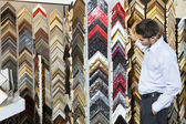 Side view of a young man browsing at a frame store with hands in pockets — Stock Photo