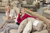 Portrait of happy mother and daughter sitting on sofa in furniture store — Stock Photo
