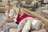 Porträt der glücklichen mutter und tochter sitzen auf dem sofa im möbelhaus — Stockfoto