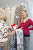 Young woman holding price list while looking at mother in furniture store — Stock Photo