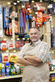 Portrait of a confident mature salesperson with arms crossed in hardware store — Stock Photo