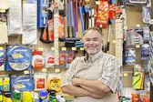 Portret szczęśliwy starsze sprzedawcy z broni przekroczył w sklepie sprzętu — Zdjęcie stockowe