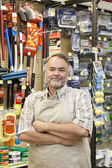 Portrait of a confident mature store clerk with arms crossed in hardware shop — Stock Photo