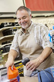 Happy mature store clerk using barcode reader at checkout counter — Stock Photo