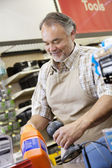 Happy mature salesperson using barcode reader at checkout counter in hardware counter — Stock Photo