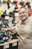 Portrait of a happy salesperson with electric saw in hardware store — Stock Photo
