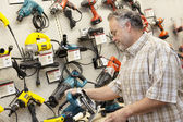 Side view of mature salesperson looking at electric saw — Stock Photo