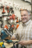 Portrait of a happy hardware store owner with electric saw — Stock Photo