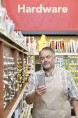 Mature salesperson reading something in hardware store — Stock Photo