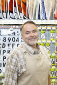 Portrait of a happy mature salesperson in hardware store — Stock Photo