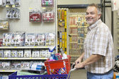 Side view portrait of a happy mature man with shopping cart in hardware store — Stock Photo