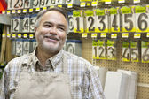 Happy mature salesperson in hardware store looking away — Stock Photo
