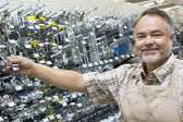 Portrait of a happy mature salesperson holding metallic equipment in hardware store — Stock Photo