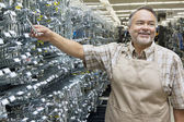 Happy mature salesperson holding metallic equipment while looking away in hardware store — Stock Photo