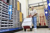 Mature man pushing handtruck in hardware store — Stock Photo