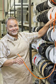 Portrait of a happy mature store clerk with electrical wire spool in hardware shop — Stock Photo
