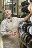 Happy mature salesperson standing by electrical wire spool while looking away in hardware store — Stock Photo