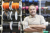 Portrait of a happy mature salesperson standing in front of electrical wire spool with arms crossed in hardware store — Foto de Stock
