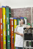 Mature salesperson standing by multicolored ladders in hardware store — Stock Photo