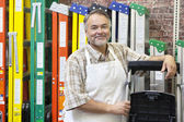 Portrait of happy mature store clerk standing by multicolored ladders in hardware shop — Stok fotoğraf