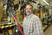 Portrait of a happy mature man holding shovel in hardware store — Stok fotoğraf
