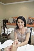 Heureux milieu femme adulte se clous polis par manucure dans un salon de beauté — Photo