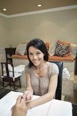 Portret szczęśliwy połowy dorosła kobieta coraz paznokcie polerowane przez manikiurzystkę w gabinecie kosmetycznym — Zdjęcie stockowe