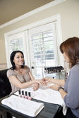 Mid adult manicurist polishing nails of beautiful happy female — Stock Photo