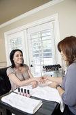 Mid adult manicurist polishing nails of beautiful happy female — Stock Photo