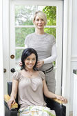 Portrait of a beautiful mid adult customer with hairstylist in beauty salon — Stock Photo