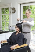 Cheerful hairstylist giving a haircut to beautiful mid adult woman in beauty salon — Stock Photo