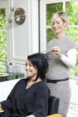 Cheerful hairstylist looking at hair of beautiful woman in beauty salon — Stock Photo