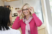 Happy senior woman trying on glasses in store — Stock Photo