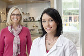 Portrait of a mid adult optometrist with female wearing glasses in background — Stock Photo