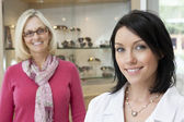 Portrait of a mid adult optician with happy female customer in store — Stock Photo